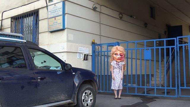 Активистка в костюме с накладной головой возле полицейского участка