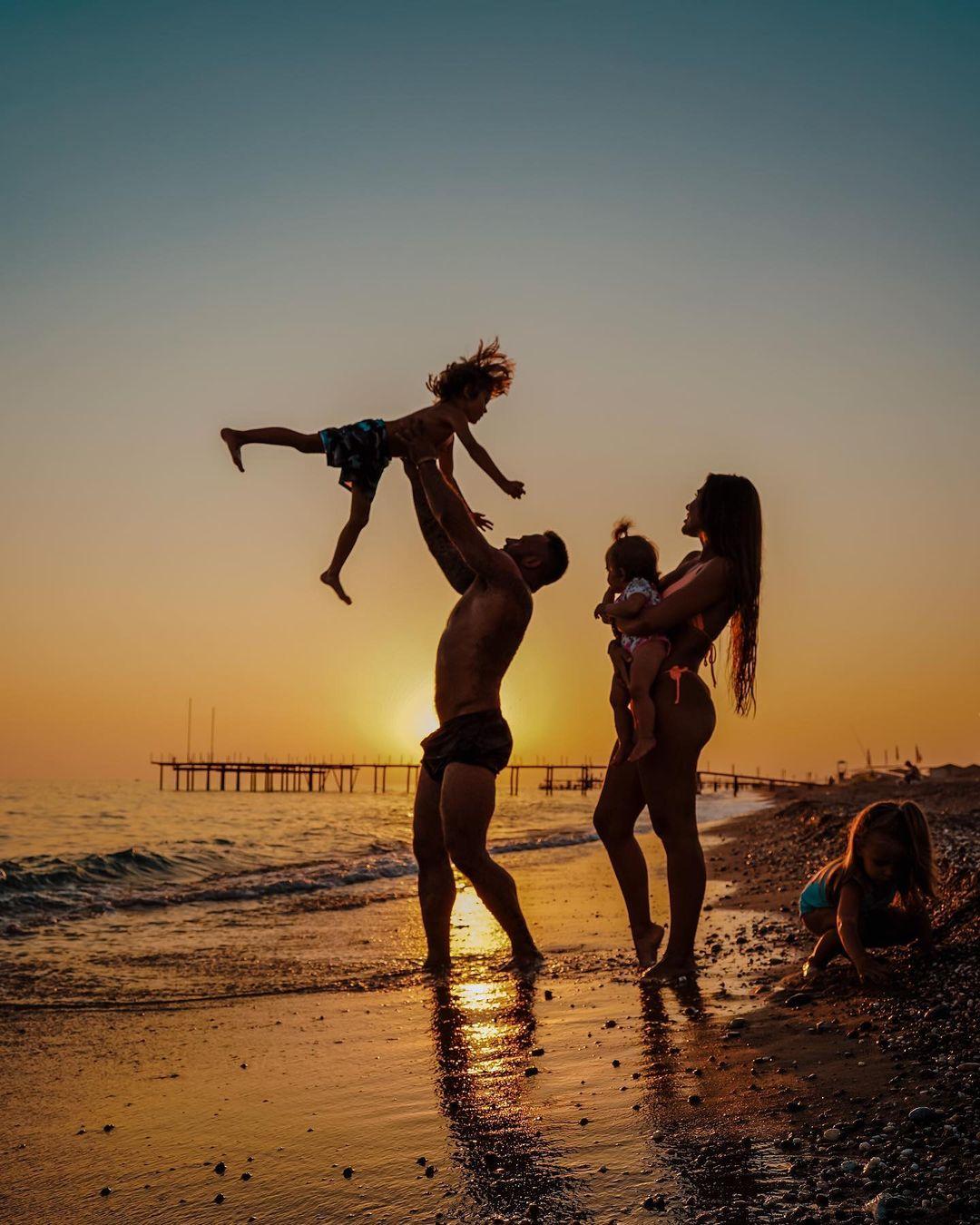 Дмитрий Стужук подбрасывает ребенка вместе с Софией Стужук на фоне заката