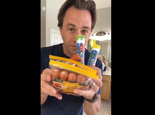 парень держит сосиски и конфеты