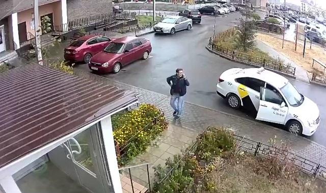 Мужчина говорит по телефону у подъезда
