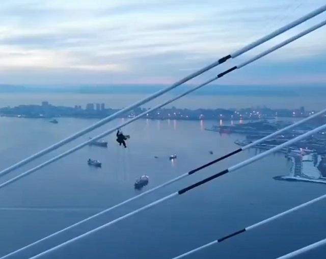 Альпинист из Владивостока очищает от наледи мост