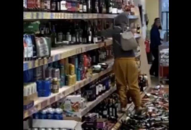 Женщина громит бутылки в магазине