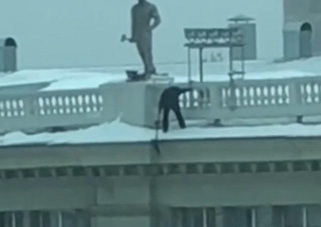 Убирает снег на крыше