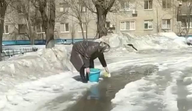 Бабушка набирает воду из лужи