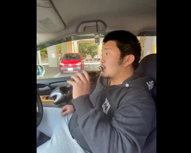 пьет колу в машине