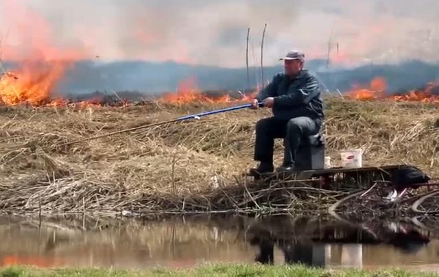 рыбак на фоне пожара
