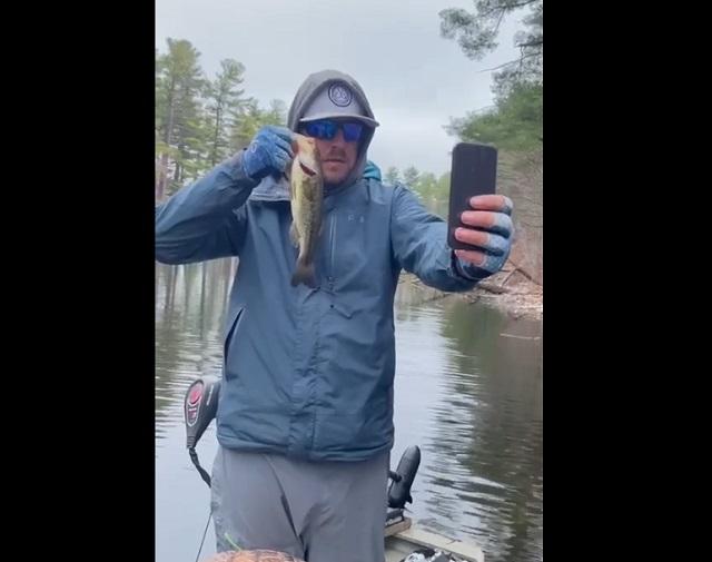 рыбак делает селфи с рыбой