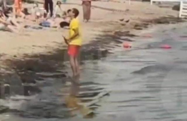 парень чистит пляж