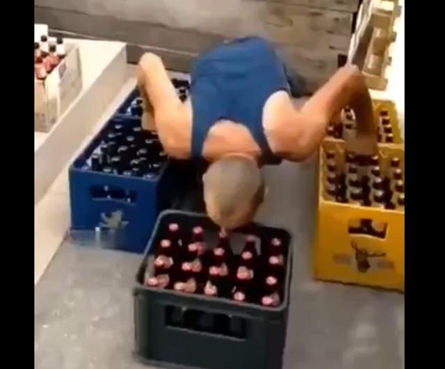 мужчина зубами поднял ящик пива