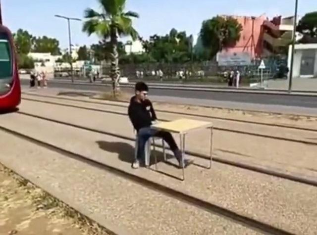парень сидит на трамвайных путях