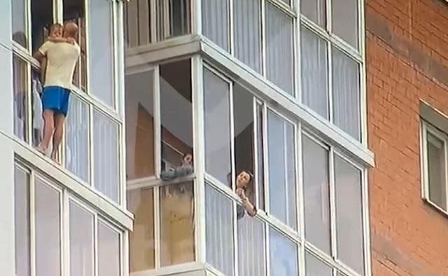 мужчина с маленьким ребенком на руках вылез на парапет балкона