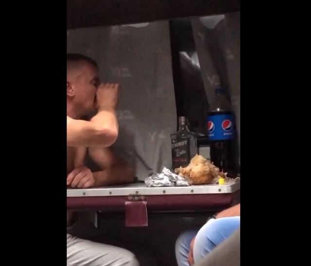 Мужчина пьет в поезде