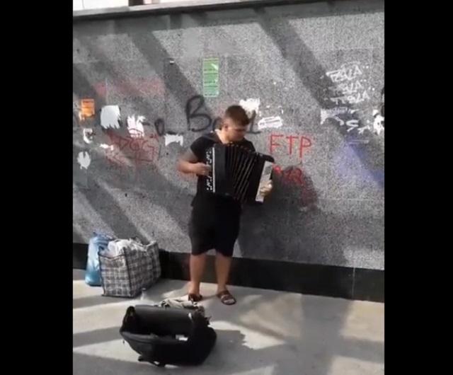 Уличный музыкант играет на баяне